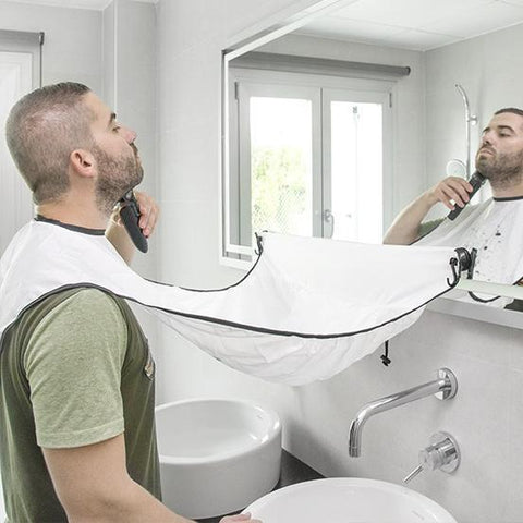 Is your girlfriend mad at you because you just shaved and now she has to unclog the sink AGAIN? Well, with our NEW Beard Trimming Catcher apron, you'll never get in trouble for that again! Featuring suction cups that lock into place on your shaving mirror, this shaving apron is the ideal catch-all for those grubby beard shavings that end up all over the bathroom counter and even worse, down the drain to form that next big clog!   Simply secure the velcro neck straps and attach the suction cups to the mirror or another smooth surface. You can use the Loop Holders for pausing sessions, then when you're done, just detach the cape, slide the hair trimmings into the trash and VOILA! No More Clogged Sinks!   By adding 10 seconds to your shaving routine, you can save yourself (or someone else) hours of cleaning time. YES, this Beard Trimming Catcher apron is the perfect choice for saving you loads of cleaning time!   100% Nylon, waterproof, washing machine safe or just hang it to dry.  Our smart, grooming apron set is a wonderful gift idea for your boyfriend, husband, dad, brothers, uncles, grandfathers and all of the other men in your life! Plus, you're doing the women in their lives a big favor too! It's a win win situation!