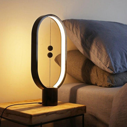 Enjoy modern vibes in an instant when you decorate your space with this cool, Wood Magnetic Table Lamp. This elegant lamp is both a desk or table lamp as well as a piece of modern art. So much more fun to turn on and off than a traditional lamp! This stylish, sleek and innovative lamp enhances and refines any space.   The Wood Magnetic Table Lamp is easy to operate. When you lift the lower magnetic ball, it's attracted to the upper magnetic ball, causing them to balance in mid air. This magnetic force then turns the lamp on. To turn the lamp off, simply disconnect the two magnetic balls.   The Magnetic Lamp is a manageable size, making it the perfect bedside light or desk lamp. The lightweight, modern design is a perfect statement piece for any home or office and it comes in a variety of colors; Black, White, Red or Natural Wood.