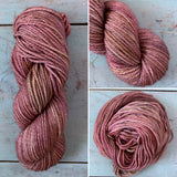 A worsted weight skien layered with warm brown, brick red, plum purple and hints of moss green.