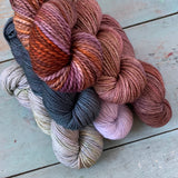 A pile of six skeins of yarn in a variety of colours.