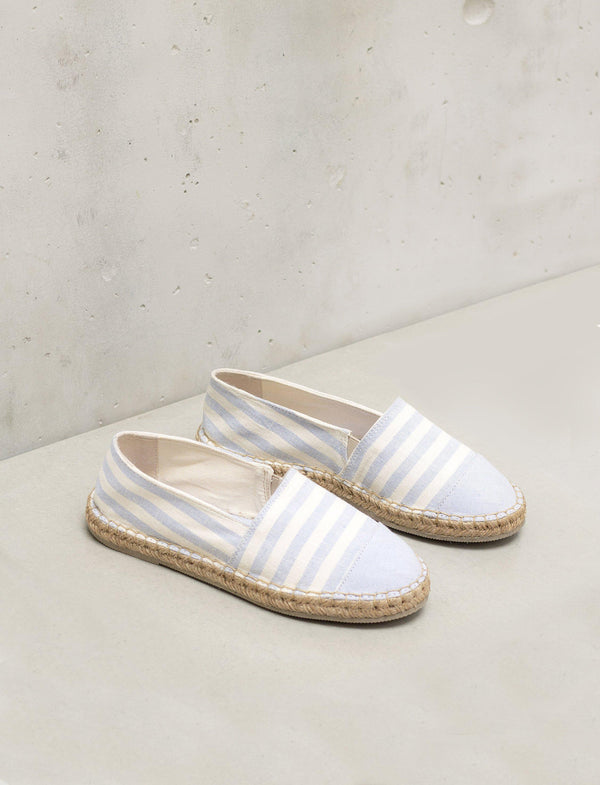A pair of white and blue espadrille shoes