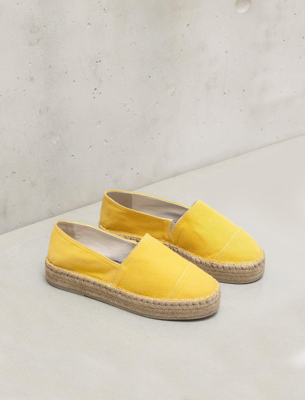 A pair of mustard color espadrille shoes