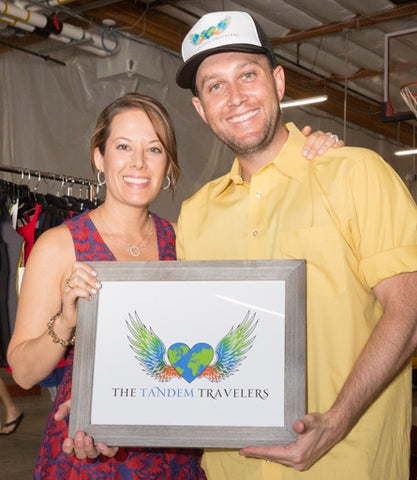 "July 2017 Launch Party ""The Tandem Travelers"" Katie and Dan holding up framed logo smiling"