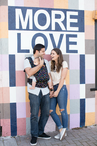 "A couple look at each other and smile while leaning on a wall that has art that reads ""More Love"". The couple is holding hands. One caregiver is holding their baby in a Tula Free-to-Grow in the Confetti Dot print."