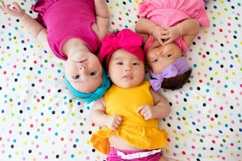 Three babies dressed in bright colors rest on top of a Tula Blanket