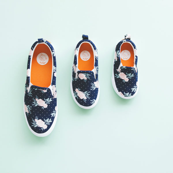 A row of Blossom Tula Shoes on a light blue background. Blossom shoes are navy with pink flowers and polka dots on them.