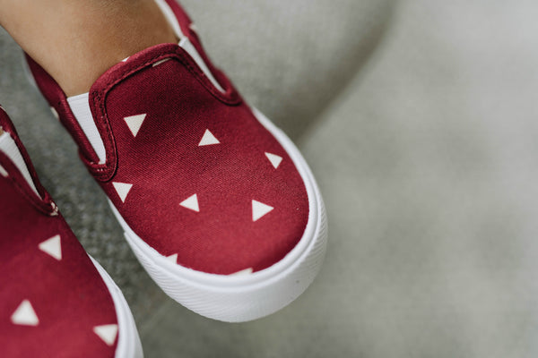 Close up of a toddler wearing Tula Shoes in the Happy Dust print. They are burgundy with small triangles.