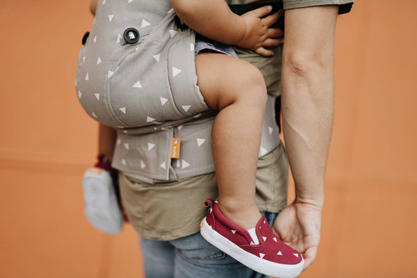 Close up of child in a back carry. They are wearing Tula Shoes that match the carrier.