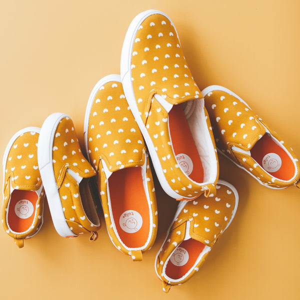 "Cluster of Play Tula Shoes on a yellow background. ""Play"" has a yellow background and repeating little white hearts all over."