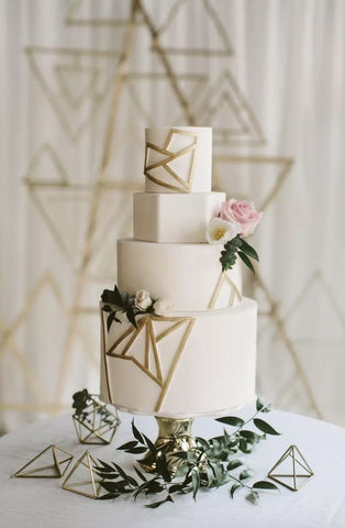 White, three-tiered wedding cake with gold geometric frosting on the sides