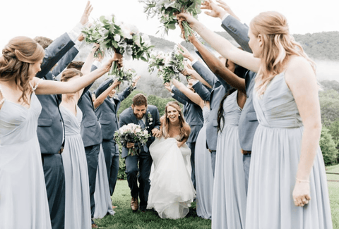 Bridesmaids and groomsmen holding up hands to make a tunnel while bride and groom run underneath