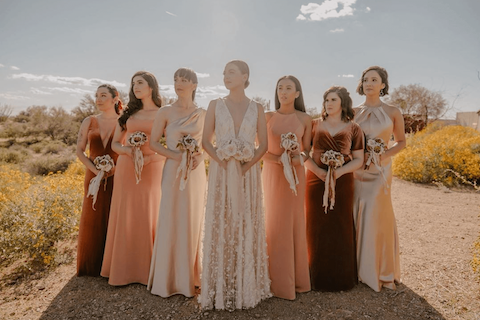 Bridesmaids standing in the dessert and holding bouquets