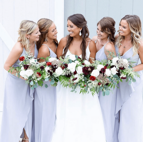 Bride and four bridesmaids carrying rose bouquets