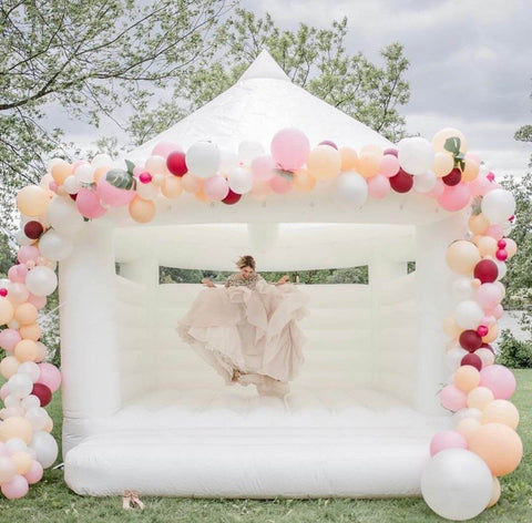 Bridesmaid in light pink dress jumping on white moonbounce