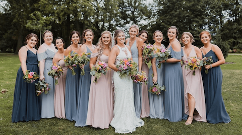 Bride and twelve bridesmaids carrying flower bouquets