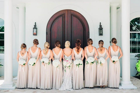 Eight bridesmaids and bride facing away from the camera holding white bouquets behind their backs