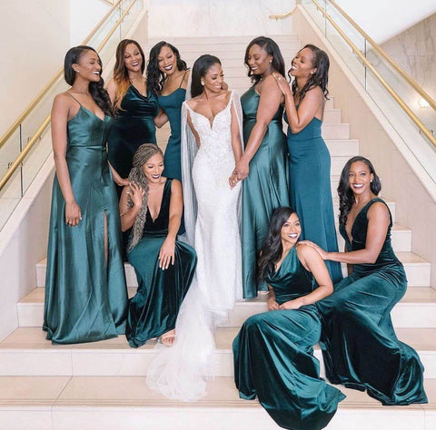 bride in white dress and bridesmaids in green dresses posing on indoor staircase