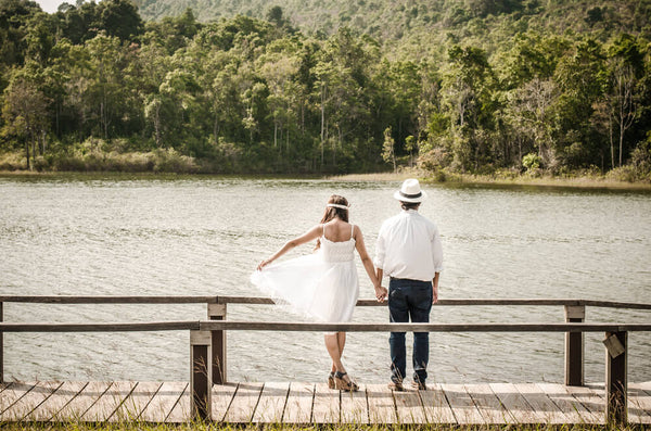 A couple facing a lake at a casual wedding.