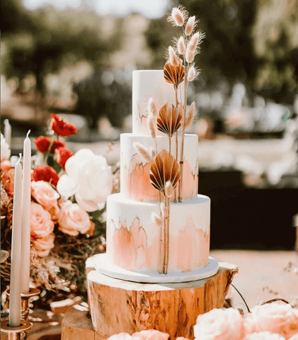 White, three-tiered wedding cake with pink watercolor washes around it