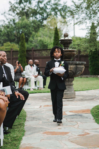 Ring bearer wearing black tux carrying white ring pillow down the aisle