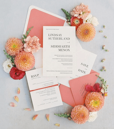 Pink and white invitation suite on a table, surrounded by white, pink, and red flowers.