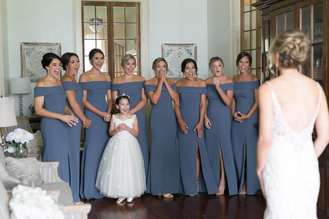 Eight bridesmaids and one flower girl looking at bride in amazement upon first reveal of her dress