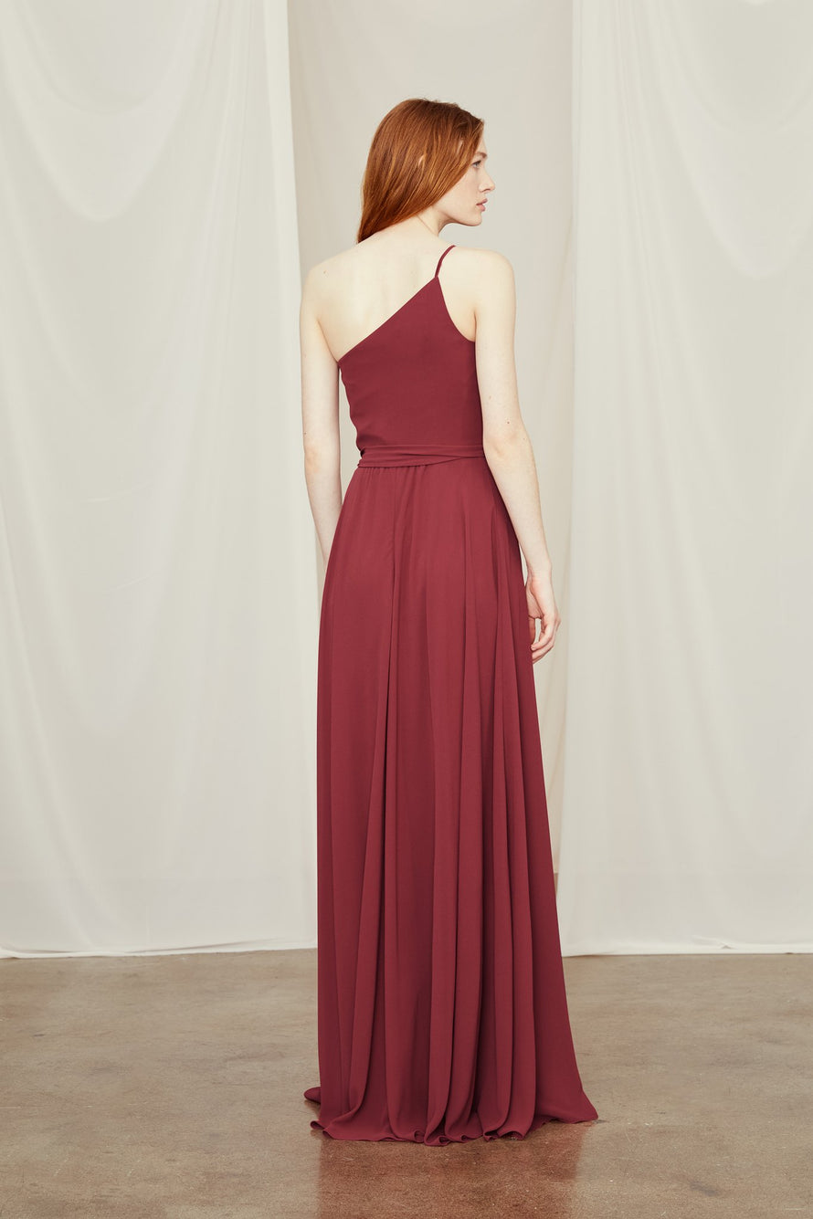 one-shoulder bridesmaid dress is accented with delicate ruching and tied at the waist above an airy skirt