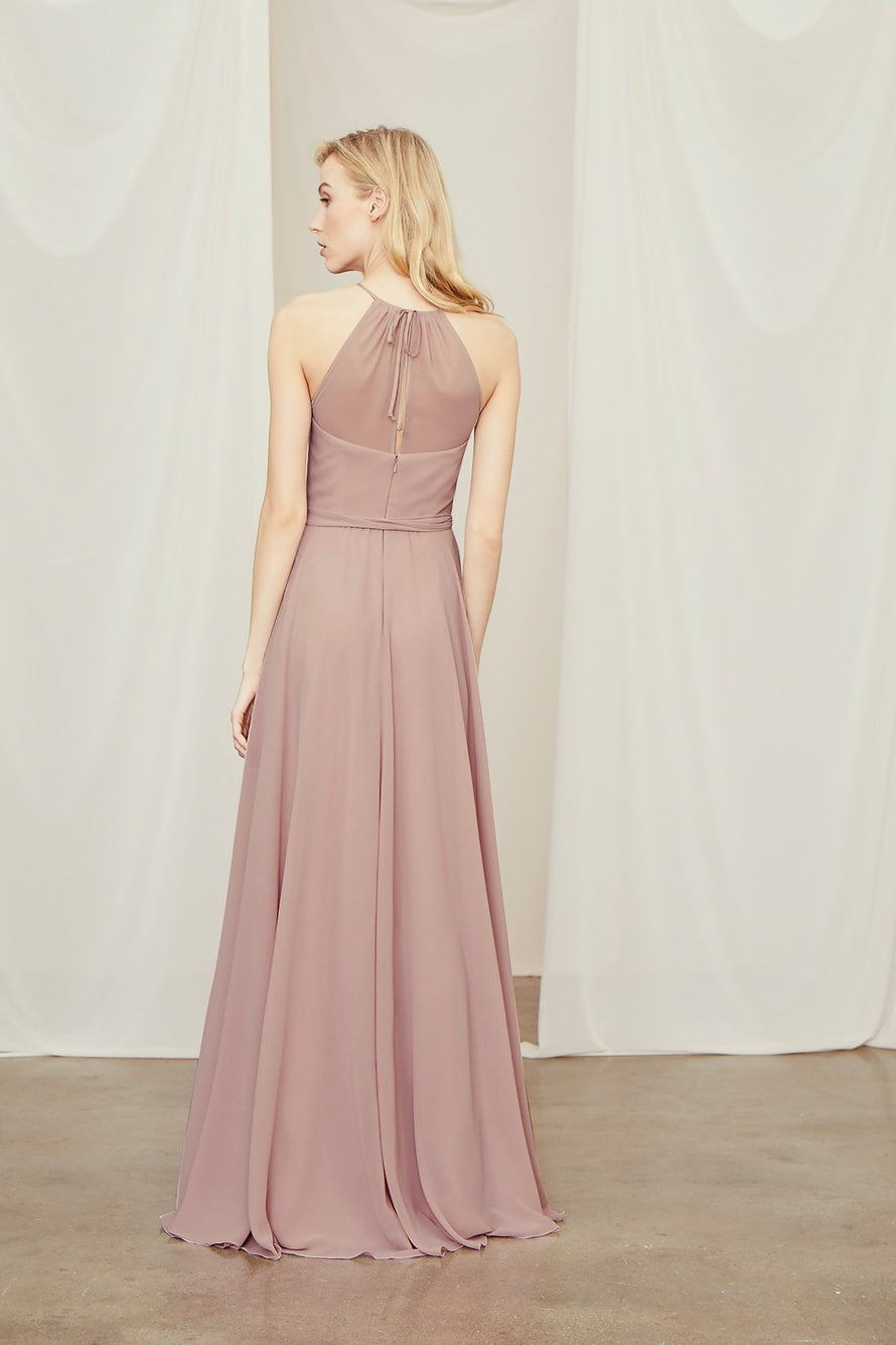 Simply flawless in chiffon, this bridesmaid dress ties at the neck above a sheer back and is finished with a belt for form-defining drape