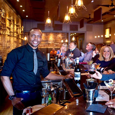 Carlton Chamblin serving guests and discussing cocktails from behind the bar