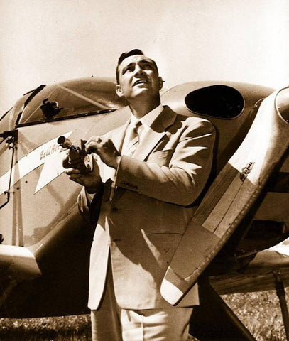 Kenneth Arnold holding his camera in front of his plane