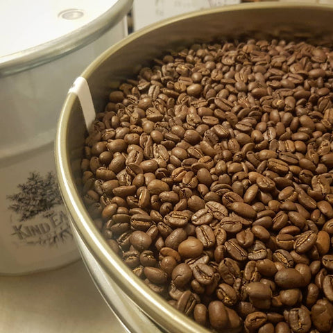 Close up of coffee beans in coffee drum. Second drum in background with lid on.