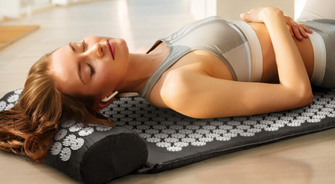 WOMAN LIES ON GRAY ACUPRESSURE MAT AND RELAXES - LIVING A SWEETER LIFE