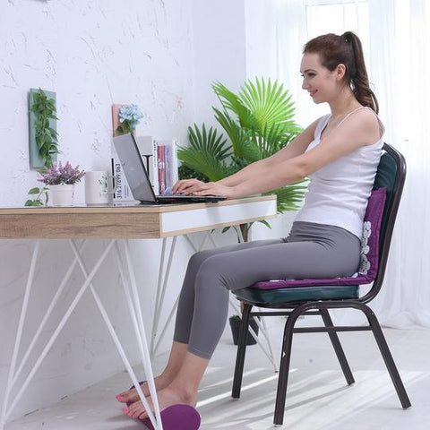 woman sits on acupressure mat and uses acupressure pillow on her feet - living a sweeter life