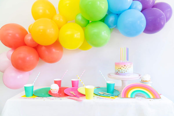 Momo party Modern rainbow party table look with colorful rainbow large paper plates, cups, pastel rainbow cake with rainbow candles, rainbow balloon garland with pink, coral, orange, yellow, lime, blue and purple latex balloon