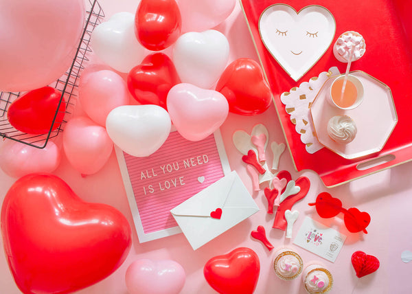 Valentine's Day Galentine's Party Ideas with Kids featuring heart-shaped latex balloons in pink, white and red and heart shaped plates in pink styled by Momo Party