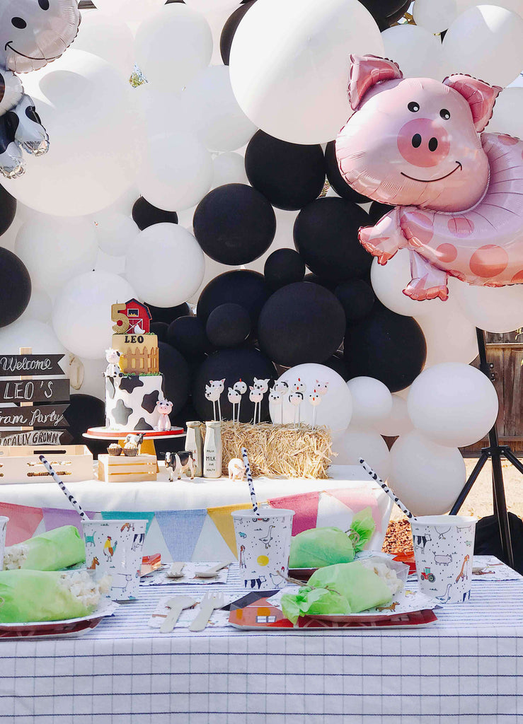 Kids Farm Barnyard Party Decoration Ideas featuring a farm animal pig foil balloon on top of a cow print inspired balloon wall