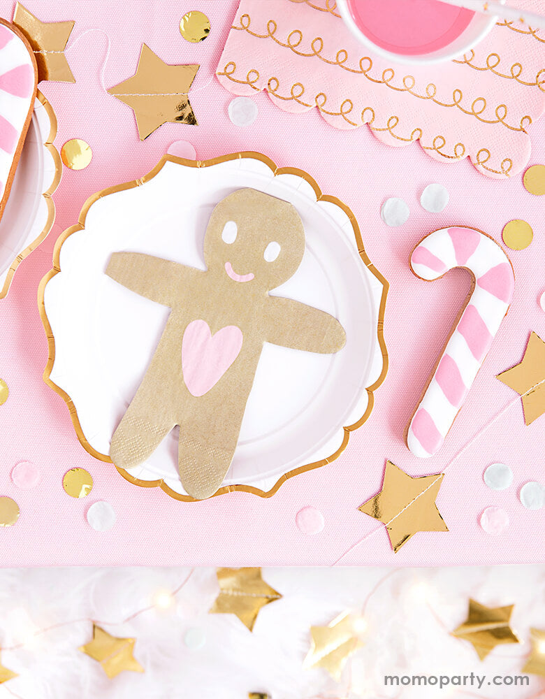 A pink Christmas party table set up featuring Party Deco's Gingerbread-Man-Napkin with star banners and candy cane sugar cookies around