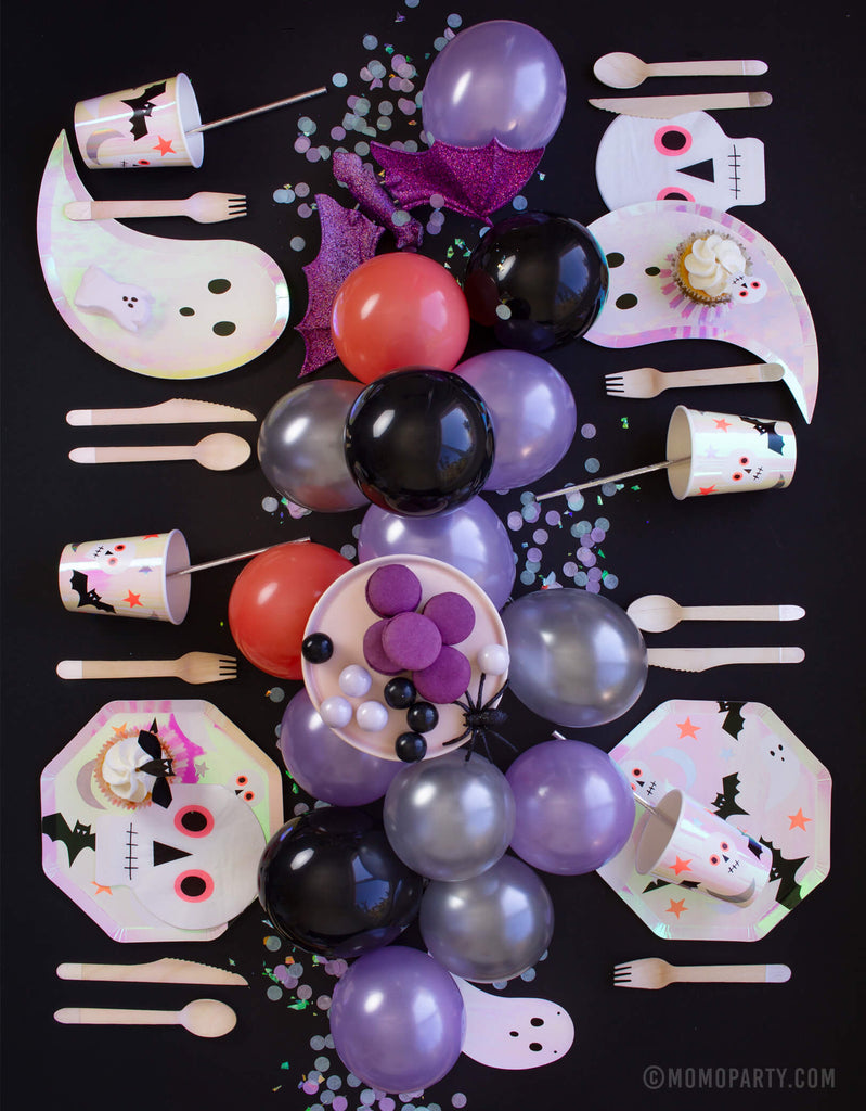 Momo Party Halloween Party table set up with halloween icon plates, iridescent ghost plates, skull napkins, and halloween icon cups, wooden utensils on the tables,  purple coral latex balloons as centerpiece