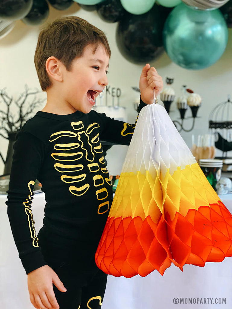 Kids Low-Contact Halloween Party Ideas by Momo Party - A boy holding candy corn decoration in a Halloween party at home