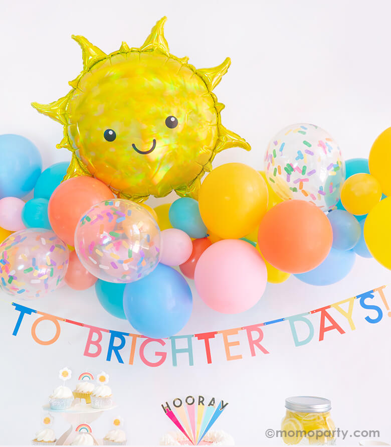 """Momo party Good Vibes Only Party Box Look, Backdrop details of Anagram Iridescent Sun Foil Mylar Balloon over a colorful blue, yellow, coral, goldenode mixed latex balloon garland with confetti latex balloons, and Meri Meri Multicolor Bunting Banner spelled as """"To Brighter Days!"""" text"""