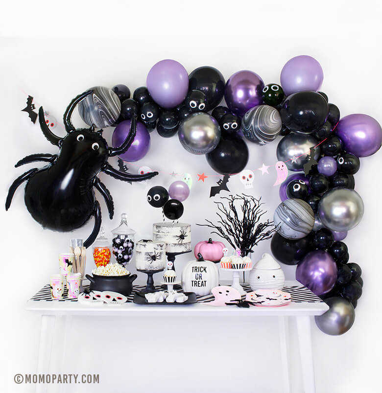 Momo Party Halloween Box look with spider balloon, chrome purple, pearl purple, black and chrome silver mixed latex balloon garland, table set up with ghost plates, halloween icon plates and cups, pink pumpkin decorations