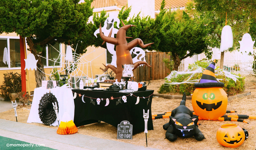 Momo Party Halloween Drive Thru Birthday Party Set up in the front yard. Dessert table decorated with Coffin cake, Halloween themed treats, MeriMeri Halloween icon garland. Halloween inflatables in the back, MeriMeri hanging ghost decoration on the tree branches