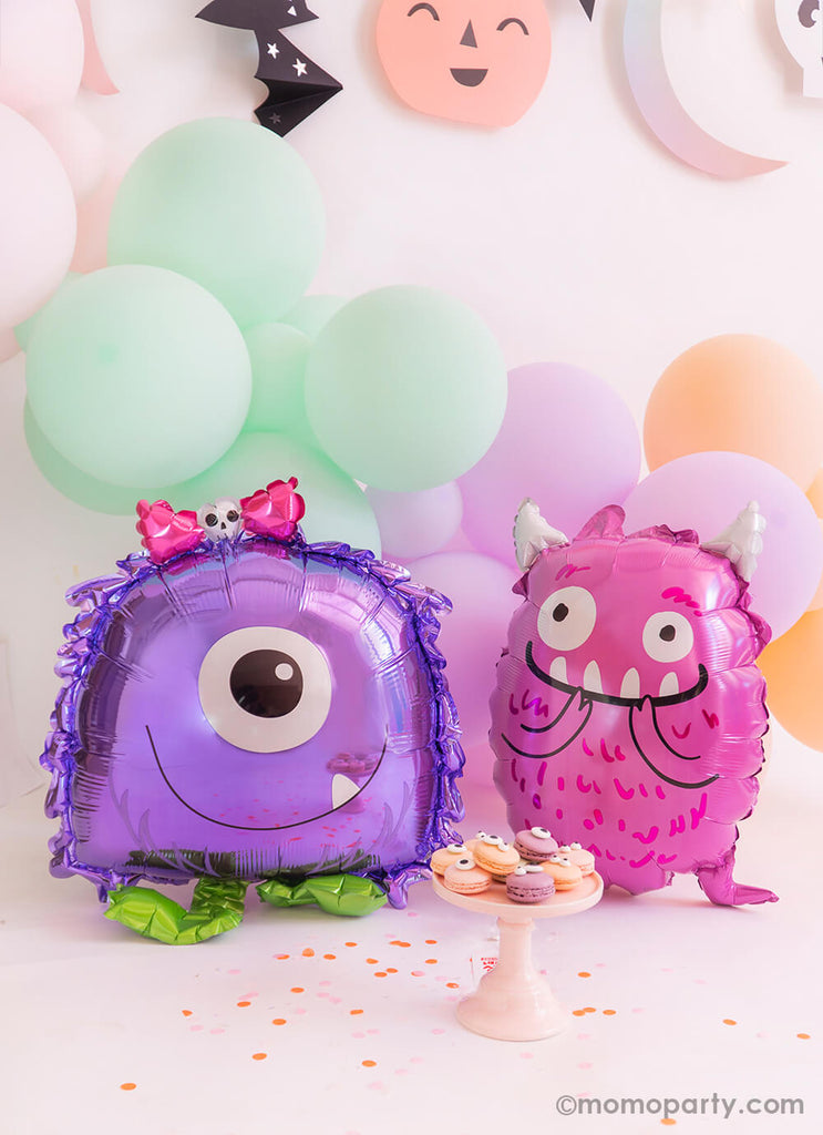 Purple Monster Balloon Buddies Airwalker Foil Balloon and Purple Monster Foil Balloon together sitting in front of the pastel Macarons with googly eyes, there are pastel balloon cloud on the back, super cute for a not so scary halloween party, little monsters party, monster bash party