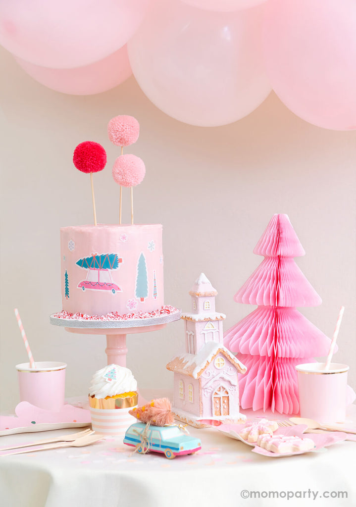 Momo-Party-Holiday Set up with Pastel pink buttercream cake decorated with Let's Get A Tree! Cakescape Edible Stickers of christmas tree on a truck, snowflakes stickers. Cake By Courtney Pom Pom Cake Toppers, Light Pink Honeycomb Paper Christmas Tree, a snow pink house decoration, pastel mint car carry a pink tree ornament, cupcake in the Blush Striped Food Cup, fa la la tree plates on the table for a modern cute sweet cozy look holiday celebration