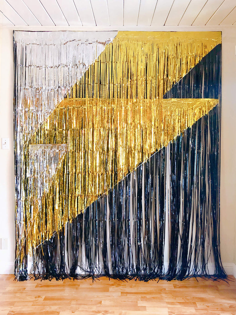 party decoration idea of lighting bolt photo booth backdrop for Morden Superhero themed birthday party, made of gold black and silver fringe curtains