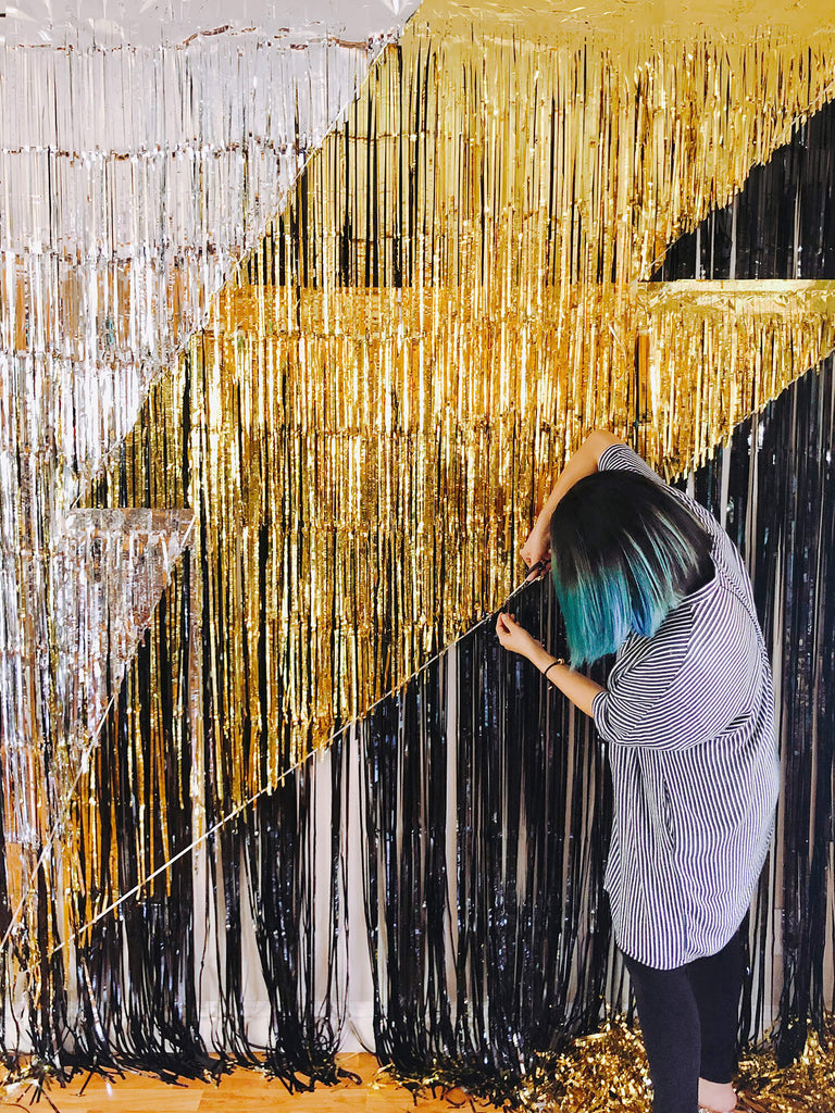 DIY tutorial of lighting bolt photo booth backdrop for Morden Superhero themed birthday party, tutorial step by step image of trimming gold fringe curtain