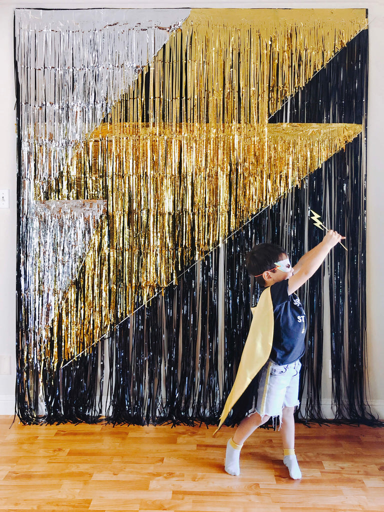 little superhero boy with mask and cape running in front of a black gold sliver fringe curtains made giant lighting bolt icon backdrop