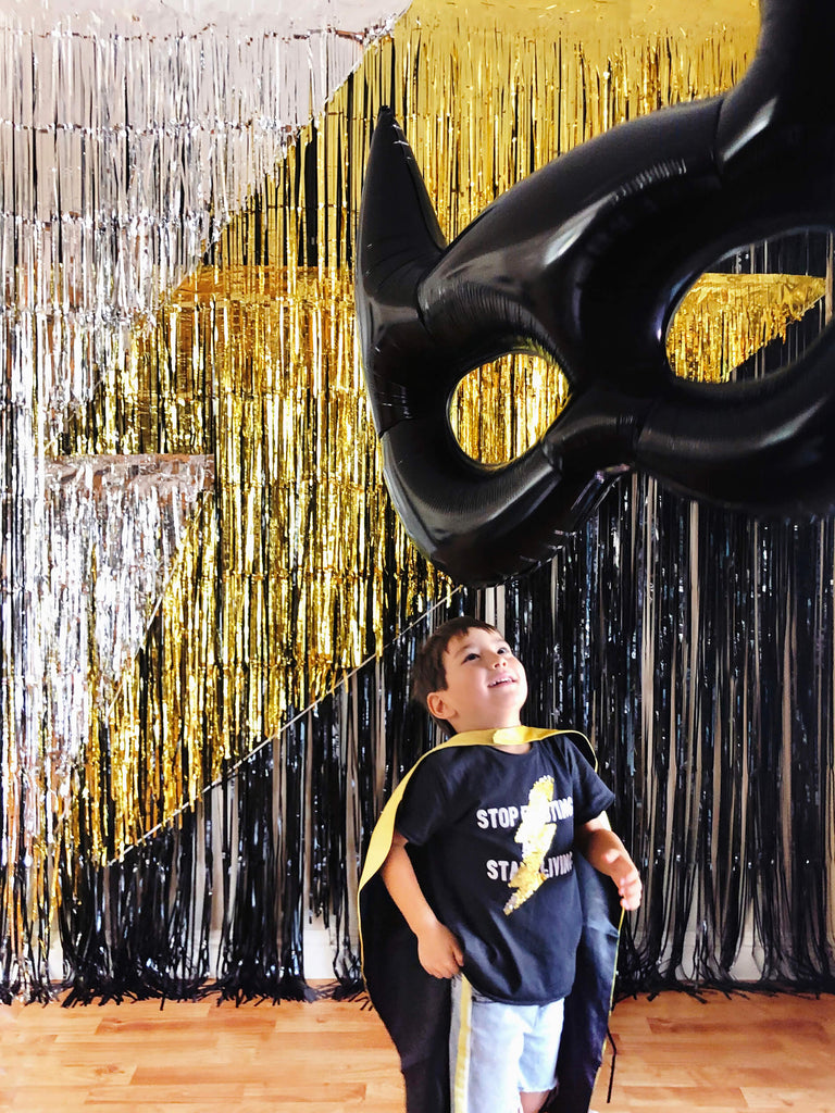 little superhero boy with black and yellow cape, looking at a giant black bat mask foil balloon in front of a black gold sliver fringe curtains made lighting bolt icon backdrop