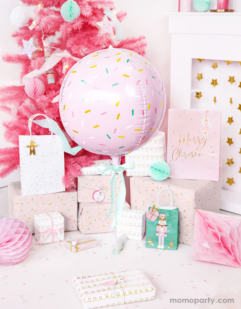 Pink Christmas party ideas by Momo Party featuring Party deco's Sprinkles-Ball-shaped-Foil-balloon-next to gifts wrapped in pastel colored paper below a pink Christmas tree