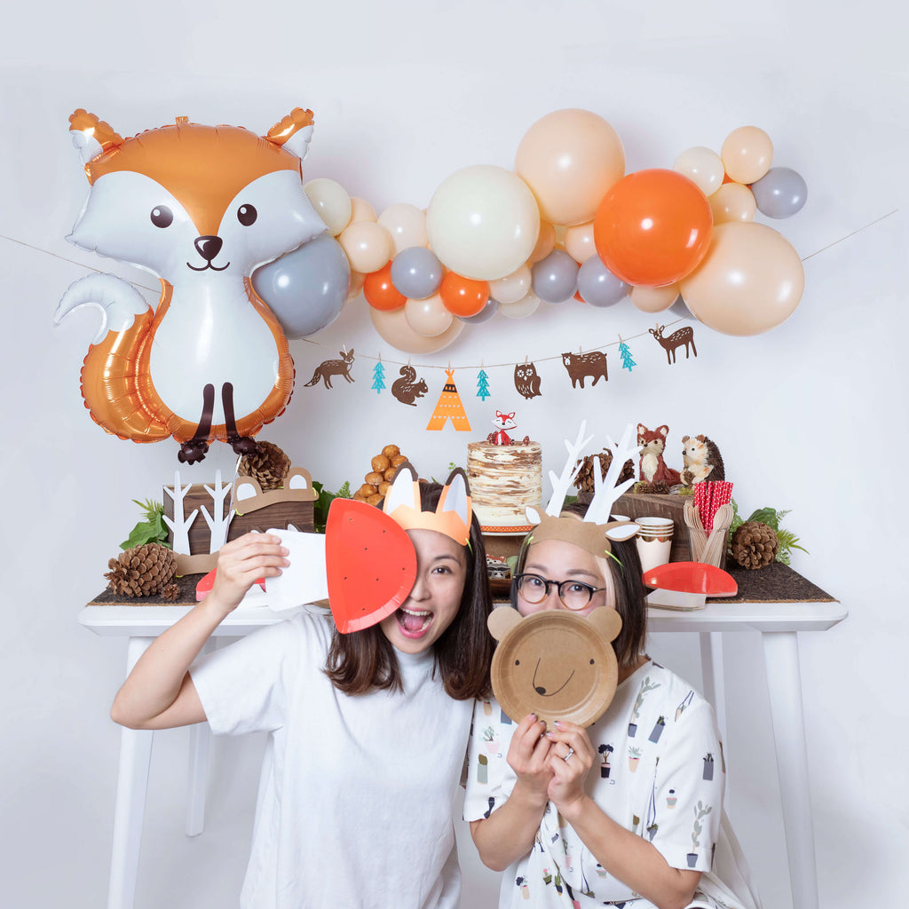 2 girls in front of woodland party with party animal hats and plates